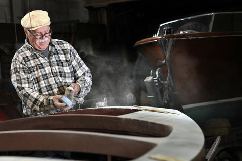 John Carl, a master woodworker, kicks up some dust as he sands a 1942 17' Chris Craft special mahogany runabout preparing it for a ninth coat of varnish.