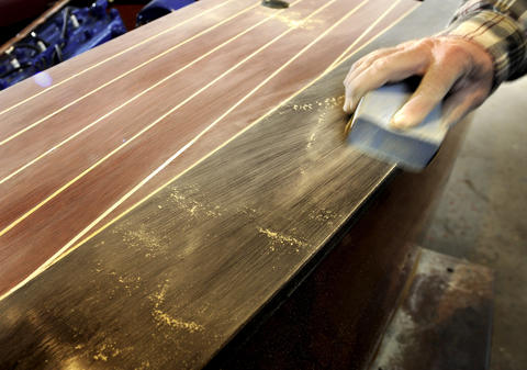 John Carl, a master woodworker, sands between coats of vsarnish on a 1942 17' Chris Craft special mahogany runabout.
