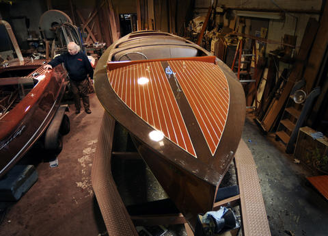Boyd Mefferd looks over a 17' 1948 Chris Craft deluxe runabout undergoing its first restoration in his shop. At right is a 27' 1937 Chris Craft triple cockpit custom runabout  undergoing a complete rstoration. More than $160,000 was spent on the woodworking alone. Another $100,000 was spent on rebuilding the original massive inboard engine.