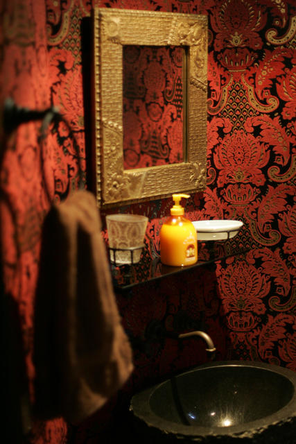 """It's a bordello look,"" Reid says of the guest powder room of will.i.am's Los Feliz studio complex. ""Pimped-out, but elegantly."" Flocked wallpaper from Astek gives the tiny room a sense of grandeur, as does the gilded Arts and Crafts style mirror, a gift from Reid."