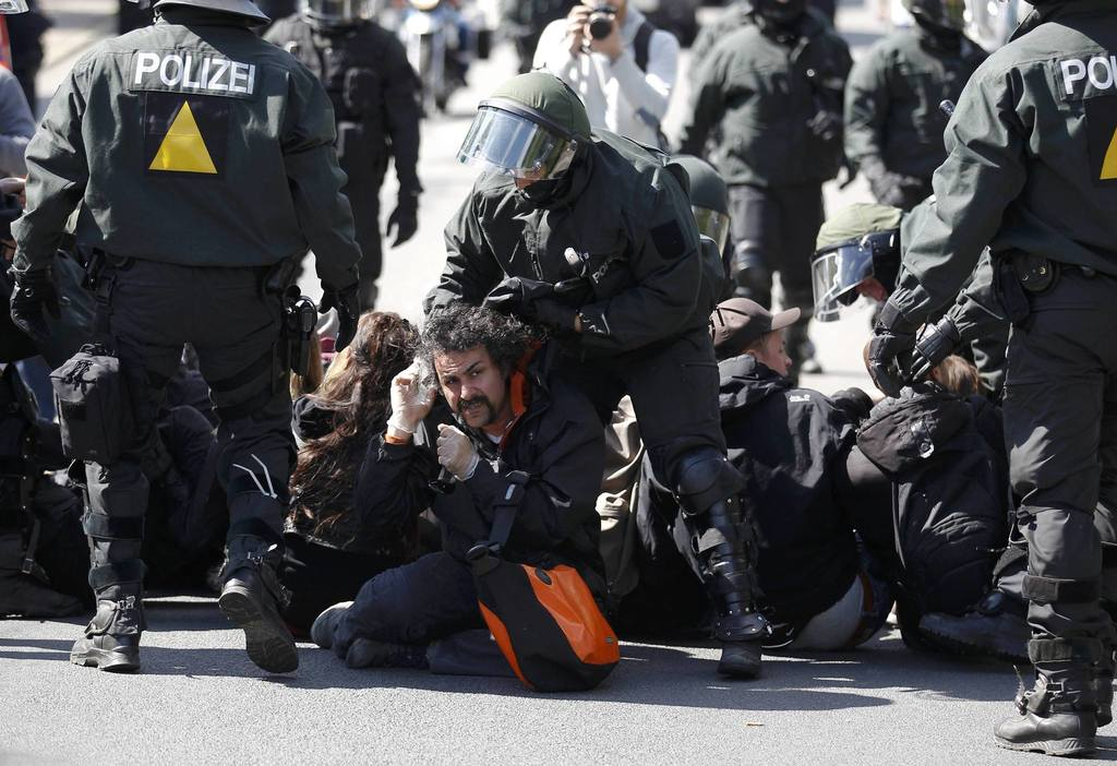 German riot police remove sitting protesters blocking the street during May Day demonstrations in Rostock, May 1, 2014.