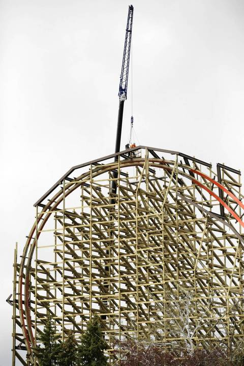 Workers are assisted by a crane as they work hundreds of feet in the air at the top of the coaster.