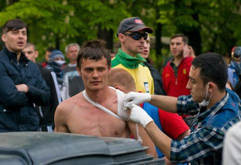 A wounded man takes treatment after clashes between supporters of a 'Single Ukraine' and Pro-Russian separatists in downtown of South-Ukrainian city of Odessa.