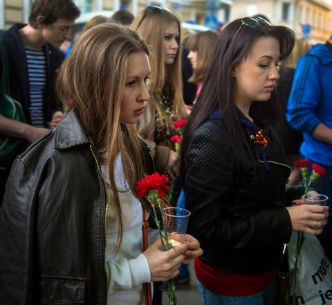 People stand near the Ukrainian embassy in Moscow during a commemoration in honor of people killed during clashes in Odessa.
