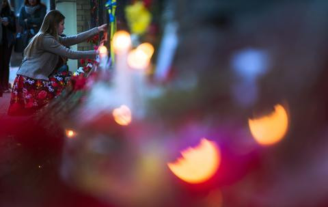 A woman lays flowers by the fence of the Ukrainian embassy in Moscow in honor of people killed during clashes in Odessa.