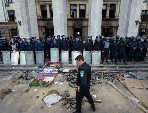 Policemen stand guard outside the charred trade union building in the southern Ukrainian city of Odessa . Flowers, candles and photos of the dead pile up outside a charred building in the scenic Ukrainian port city where anger simmers a day after brutal clashes claimed dozens of lives.