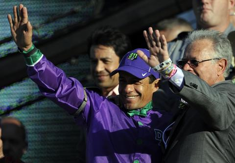 Victor Espinoza (left) and trainer Art Sherman in the winner's circle after their horse California Chrome wins the 2014 Kentucky Derby at Churchill Downs.