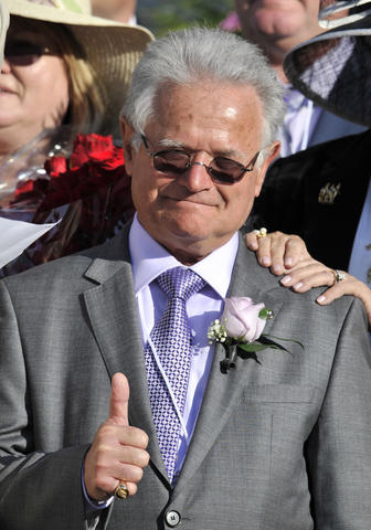 Art Sherman, the trainer for California Chrome, celebrates in the winner's circle after the 2014 Kentucky Derby at Churchill Downs.