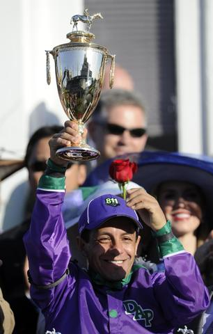 Victor Espinoza hoists the winner's trophy after riding California Chrome to victory during the 2014 Kentucky Derby at Churchill Downs.