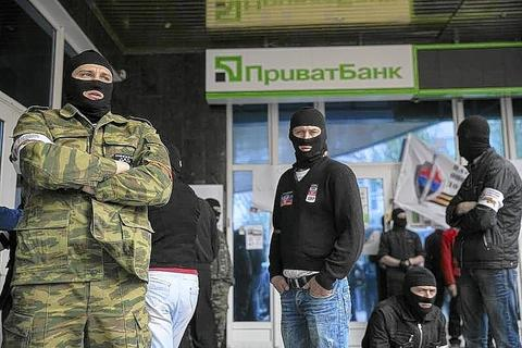 Masked pro-Russian activists stand outside a branch of Ukraine's Privatbank during a protest in Donetsk on May 5.