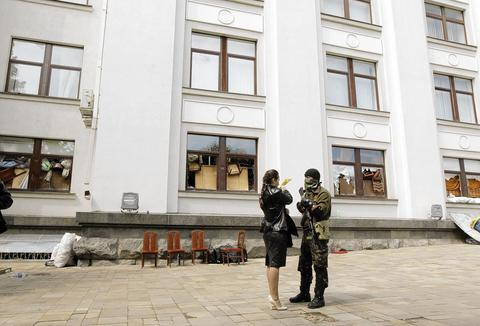 An armed and masked pro-Russian activist talks with a woman at a seized regional government headquarters in Luhansk in eastern Ukraine on May 4.