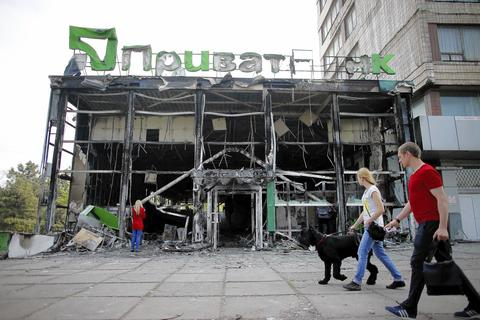 People walk past a gutted branch of Privatbank near the town hall in Mariupol in eastern Ukraine.