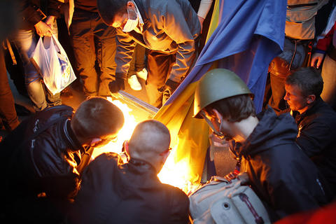 Pro-Russia protesters burn a Ukranian flag outside the district council building in Donetsk in eastern Ukraine on May 4.