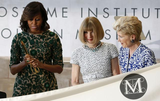 First lady Michelle Obama (L) stands beside Vogue fashion editor Anna Wintour (C) at a ceremony to open the Anna Wintour Costume Center.