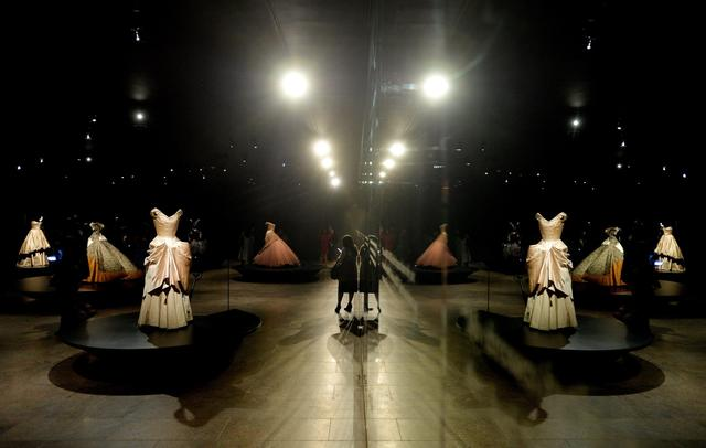 People look over dresses during a preview of the exhibit 'Charles James: Beyond Fashion' at the Anna Wintour Costume Center.