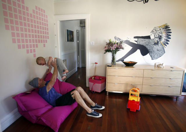 Scott Flora, on a Fatboy beanbag chair, lifts daughter Aja in the living room of his Venice home. The Heart Breakout decal above them was conceived by Hybrid Design and produced by Flora's company, Blik. David Bray's decal, I Never Saw the Sign, hangs atop a dresser used as a sideboard.