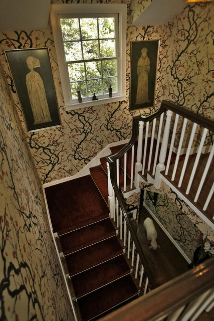 "In modern L.A., artist Lisa Borgnes Giramonti is dedicated to old England. ""I've always wanted to go back to England, but it's not going to happen, so this is how I'm re-creating that,"" she says. Here, the stairwell is lined with Flowering Quince wallpaper by Clarence House."