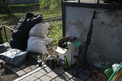 A pro-Russian armed man guards a checkpoint on a railroad track near the town of Slaviansk in eastern Ukraine on May 6.