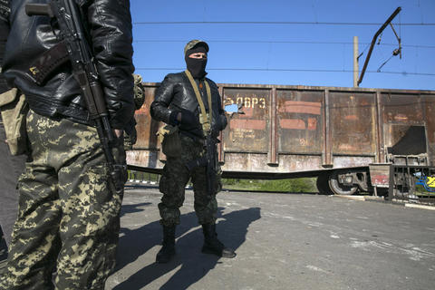 Pro-Russian armed men guard a checkpoint on a railroad track near the town of Slaviansk in eastern Ukraine on May 6.