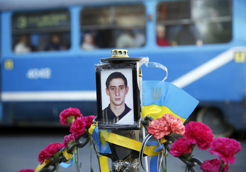 A tram passes a portrait of Andriy Biryukov, a pro-Ukrainian activist killed in clashes on Friday, at his funeral in Odessa on May 6.