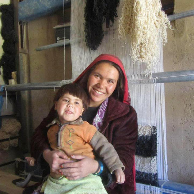 an arzu weaver poses with her child in front of her loom elissa
