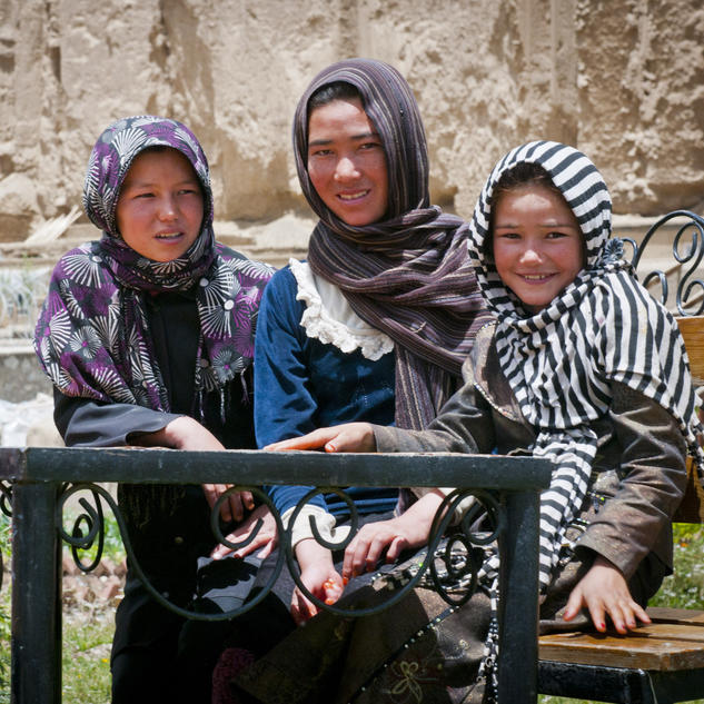 three local afghan girls sit in the arzu studio hope garden and