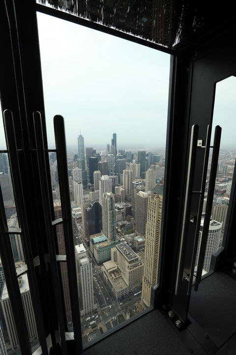 "The John Hancock Observatory will open a new attraction called ""Tilt!"" which has viewers stand against one of 8 glass panels that tilt out and down on an angle from the observatory."