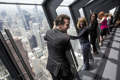 """Michael Gatti, center, tries out the new """"Tilt!"""" attraction on the 94th floor of the John Hancock Center in Chicago, Ill., on Thursday, May 8, 2014."""