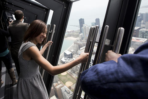 """Crystal Williams, left, of Chicago, takes in the view on the new """"Tilt!"""" attraction on the 94th floor of the John Hancock Center in Chicago, Ill., on Thursday, May 8, 2014."""