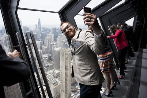 """Joel Mora, of Chicago, takes a self portrait on the new """"Tilt!"""" attraction on the 94th floor of the John Hancock Center in Chicago, Ill., on Thursday, May 8, 2014."""