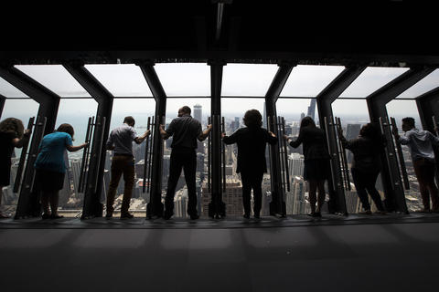 """Guests try out the new """"Tilt!"""" attraction on the 94th floor of the John Hancock Center in Chicago, Ill., on Thursday, May 8, 2014."""