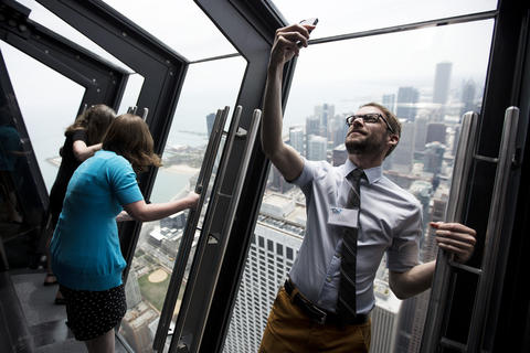 """Tony Palombi, right, of Chicago, takes a self portrait on the new """"Tilt!"""" attraction on the 94th floor of the John Hancock Center in Chicago, Ill., on Thursday, May 8, 2014."""