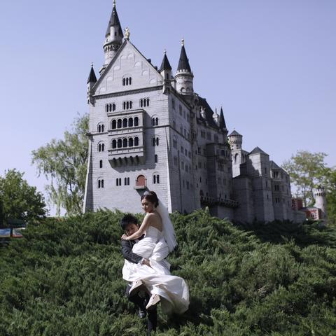 A groom carrying his bride away from a mini replica of a German style castle in Beijing World Park, in suburb Beijing.