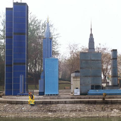 Chinese wearing traditional emperor costume sitting before a mini replica of the world trade center twin towers in Beijing World Park, in suburb Beijing.