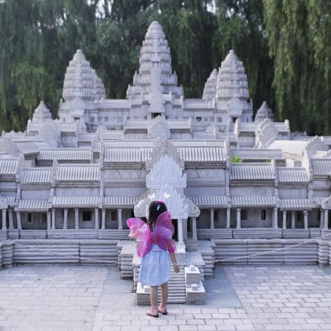 A little girl standing before a mini replica of Angkor Wat in Beijing World Park, in suburb Beijing.