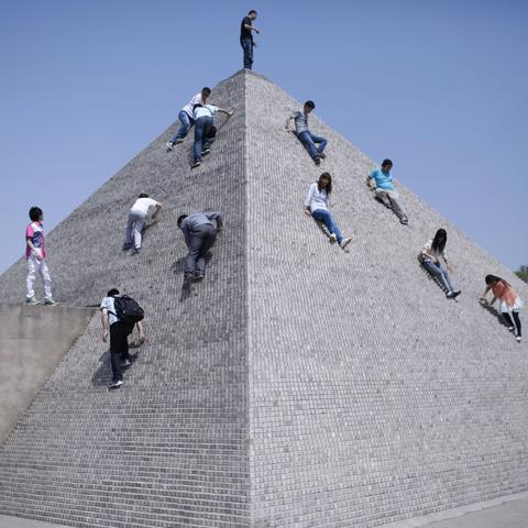 Tourists climbing a mini replica of a pyramid in Beijing World Park, in suburb Beijing.