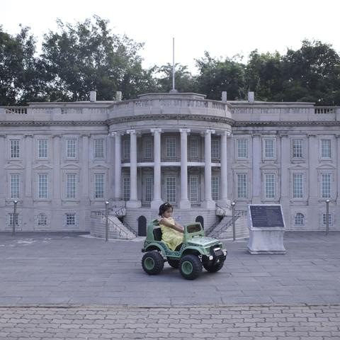 A girl playing in a toy car before a mini replica of the White House in Beijing World Park, in suburb Beijing.
