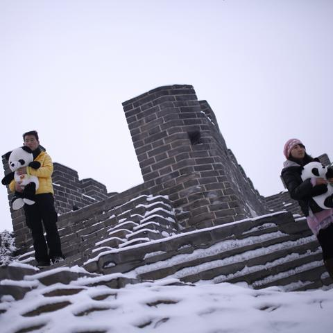 Tourists posing for photos by a mini replica of the Great Wall in Beijing World Park, in suburb Beijing.