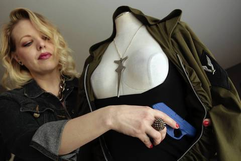 Fashion designer Sarah Church demonstrates how a stylish dress, shown unzipped, can conceal a weapon with the help a specially designed camisole that has pockets and sleeves.