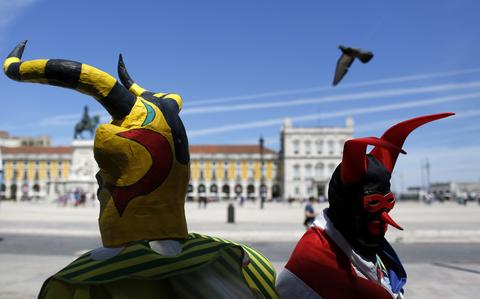 Masked people await the start of the parade of the 9th International Festival of the Iberian Mask in Lisbon May 10, 2014. The festival runs until next Sunday and about 450 masked people from Spain, Portugal and Italy are participating.