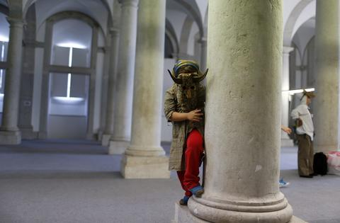 A masked child plays at a column before the parade of the 9th International Festival of the Iberian Mask in Lisbon May 10, 2014. The festival runs until on next Sunday and particle 450 masked people from Spain, Portugal and Italy.