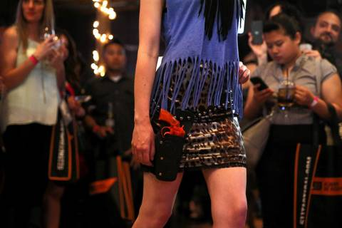 A model carries a fake plastic gun in a holster as she walks the runway during the Firearms & Fashion Show at Firewater Saloon.