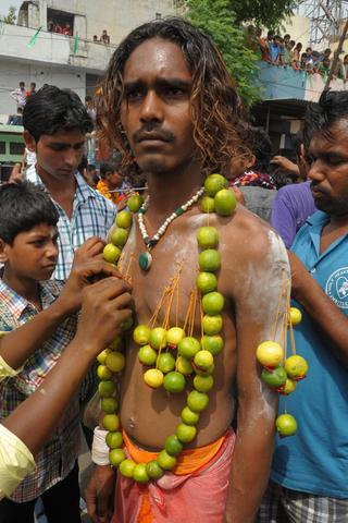 A devotee has his chest pierced with needles and lemons during a procession to honour the Hindu goddess Maha Mariamman (Sheetla Mata), to mark Mother's Day, in Amritsar on May 11, 2014 . Devotees believe that the goddess protects whoever worships her.