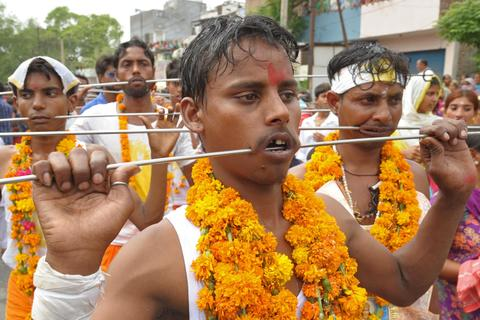 Indian Hindu devotees walk with steel rod piercings through their cheeks during a procession to honour the Hindu goddess Maha Mariamman (Sheetla Mata), to mark Mother's Day, in Amritsar on May 11, 2014. Devotees believe that the goddess protects whoever worships her.