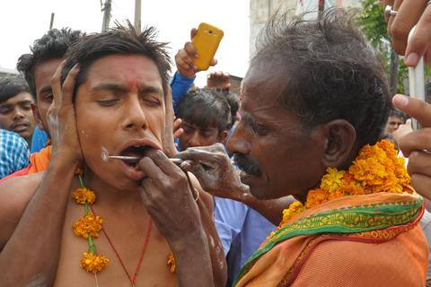 An Indian Hindu devotee gets his cheeks pierced with a steel rod known as Trishula by a Hindu Priest during a procession to honour the Hindu goddess Maha Mariamman (Sheetla Mata), to mark Mother's Day, in Amritsar on May 11, 2014. Devotees believe that the goddess protects whoever worships her.