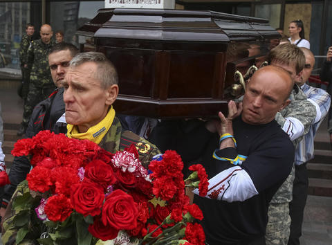 People carry a coffin containing the body of Rodion Dobrodomov, a member of the Ukrainian National guard killed during a pitched battle in Mariupol on Friday, at his funeral in Kiev on May 12.