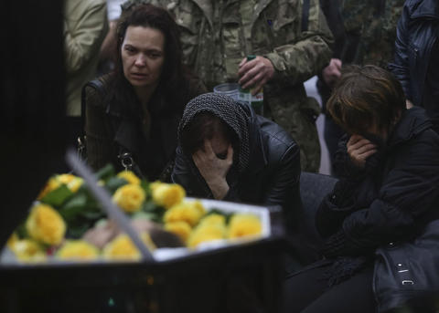 Mourners grieve at the coffin of Rodion Dobrodomov, a member of the Ukrainian National guard killed during a pitched battle in Mariupol on Friday, at his funeral in Kiev on May 12.