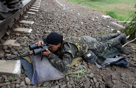 An armed pro-Russian fighter takes position at a checkpoint near the eastern Ukranian city of Slavyansk on May 12.