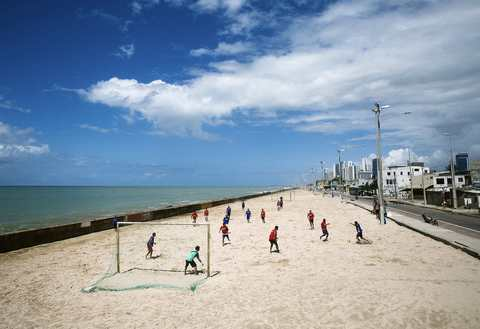 """A view of a Sunday """"pelada"""" soccer match on the beach in the Brasilia Teimosa district of Recife, a World Cup host city, May 4, 2014."""