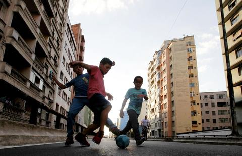 """Boys play a Sunday """"pelada"""" soccer match on a street closed to traffic for the day in Sao Paulo, a World Cup host city, May 4, 2014."""